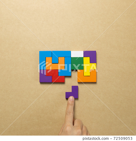 Set of color blocks puzzle pieces and hand holding last one piece on brown background. Creative thinking, idea, problem solving, success concept. top view 72509053