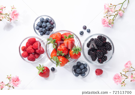 Berries in glass bowls and roses on white background. Top view. 72513700