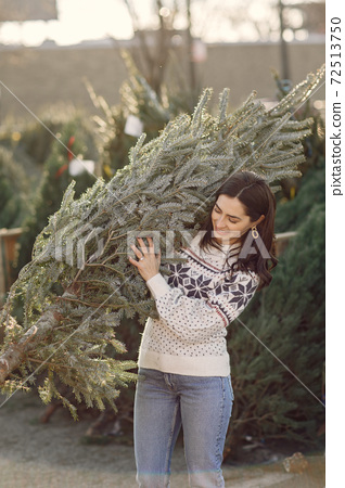 Cute brunette in a white sweater with Christmas tree 72513750