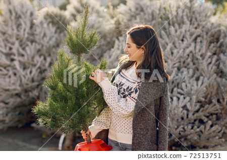 Cute brunette in a white sweater with Christmas tree 72513751