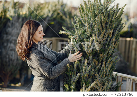 Cute brunette in a white sweater with Christmas tree 72513760