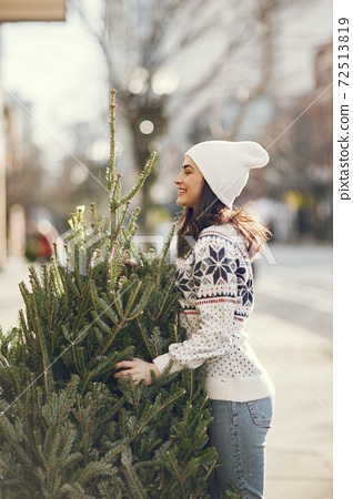 Cute brunette in a white sweater with Christmas tree 72513819