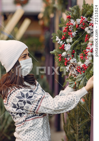 Cute brunette in a white sweater with Christmas tree 72513824