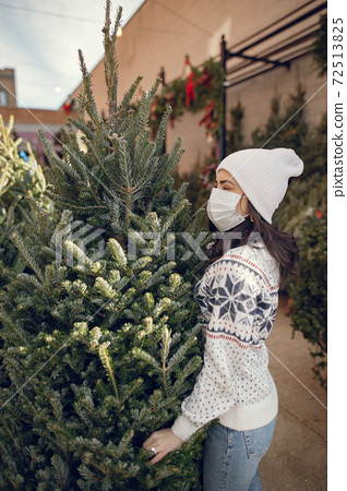 Cute brunette in a white sweater with Christmas tree 72513825