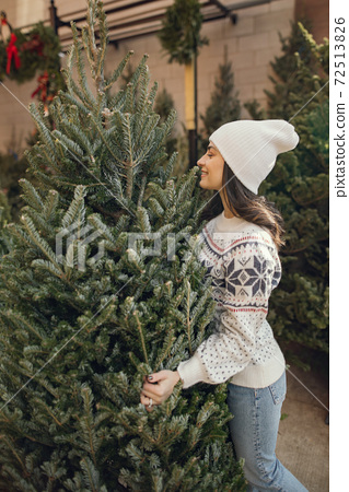 Cute brunette in a white sweater with Christmas tree 72513826