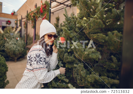 Cute brunette in a white sweater with Christmas tree 72513832