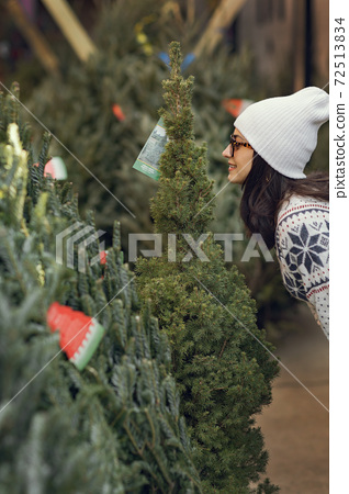 Cute brunette in a white sweater with Christmas tree 72513834