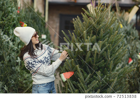 Cute brunette in a white sweater with Christmas tree 72513838