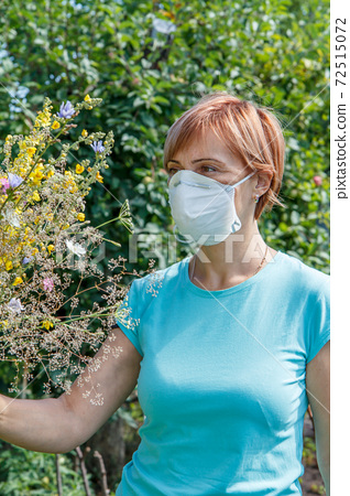 Woman in protective mask holding bouquet of wildflowers. 72515072