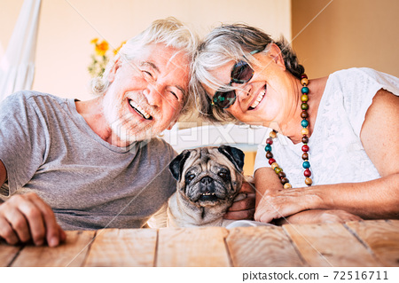 Happy couple of senior caucasian people have fun and smile with funny nice old dog pug in the middle sitting on the table together with them - retired matures with animals concept 72516711