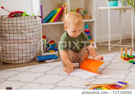 The baby is looking at an open book in the playroom 72519898