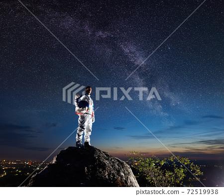 Astronaut standing on rocky mountain under night starry sky. 72519938