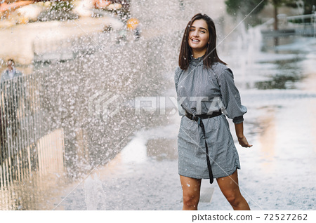 girl playing and dancing around on a wet street 72527262