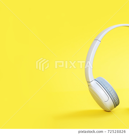 Wireless gray headphones with mobile on illuminating yellow background 72528826