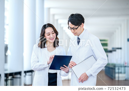 Medical image of men and women in lab coats meeting at the hospital 72532473
