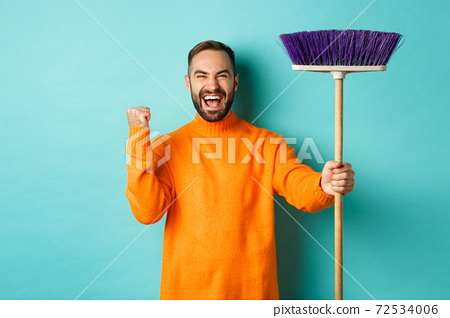 Image of encouraged and motivated man getting ready for cleaning, holding broom and making fist pump gesture, standing over turquoise background 72534006