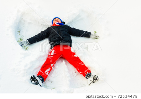 An angel in the snow made by a boy. 72534478