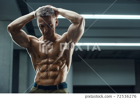 Fitness man pumping up abs muscles in gym 72536276