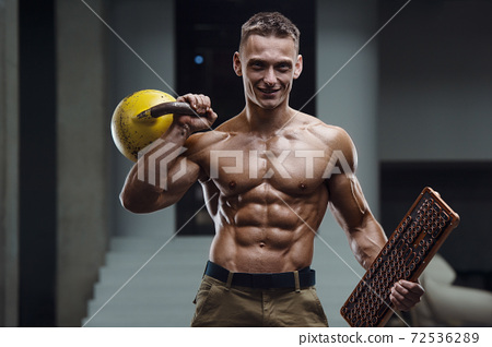 Fitness man pumping up muscles with kettlebell 72536289