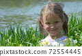 Portrait of a smiling little girl in the grass 72554445