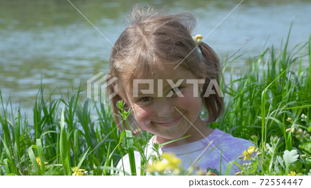 Portrait of a smiling little girl in the grass 72554447
