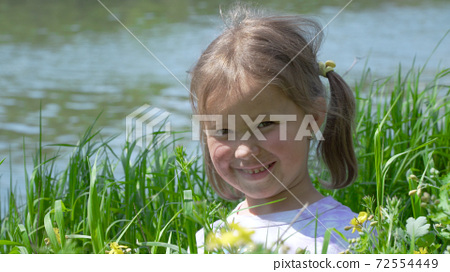 Portrait of a smiling little girl in the grass 72554449