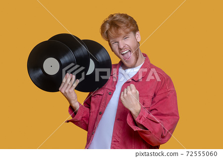 Red-haired bearded young man in red jacket with a record feeling awesome 72555060