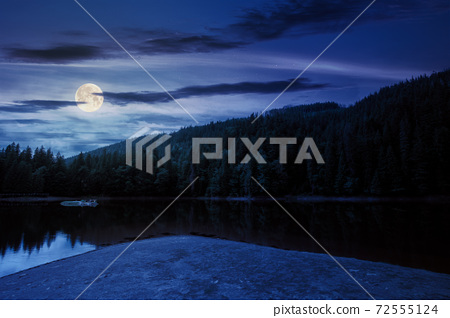 scenery around the lake in mountains at night. spruce forest on the shore. reflection in the water in full moon light. weather with clouds on the sky 72555124
