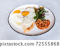 Delicious English breakfast with two fries eggs, beans, and salad on marble table. 72555868