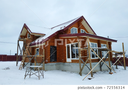 Beautiful unfinished wooden house with round logs in the countryside 72556314