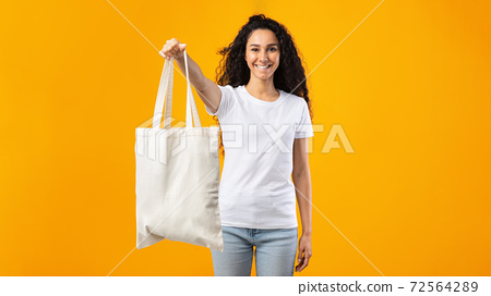 Woman Showing White Eco Bag Standing Over White Studio Background 72564289