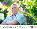 Senior man in light blue striped shirt near lush green bush 72572070