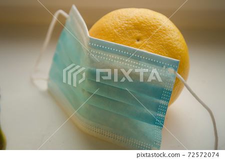 Tangerine and protective mask on white table closeup 72572074
