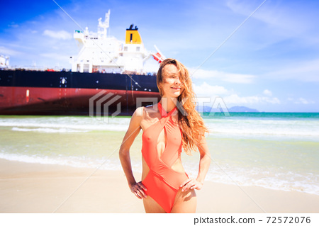 Happy woman in orange swimsuit on beach against cargo ship 72572076