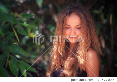 Happy woman near green tree leaves on blurred background 72572077
