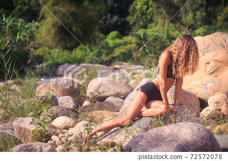 Seductive woman with long legs sitting on large stones 72572078