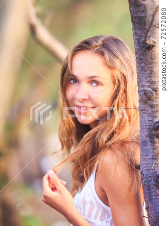 Pretty young woman in lacy clothes standing near young tree 72572080