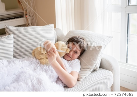 The sick boy is lying on the sofa hugging his teddy bear. 72574665