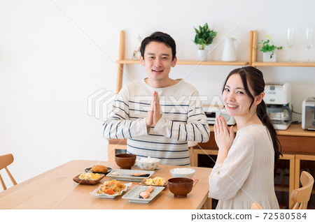 식당에서 식사를하는 젊은 부부받습니다 72580584