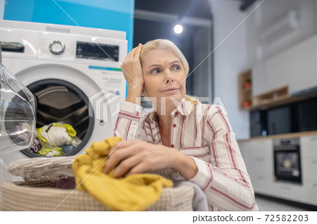 Blonde woman sitting near washing machine and looking thoughtful 72582203
