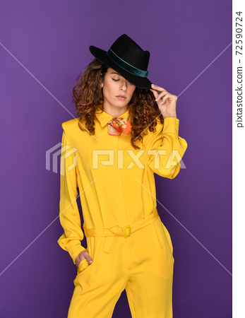 Fashionable woman in yellow 80s suit and hat 72590724