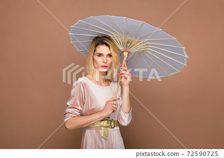 Elegant lady in chenille suit with parasol 72590725