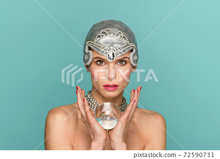 Chic woman in tiara holding a glass ball 72590731