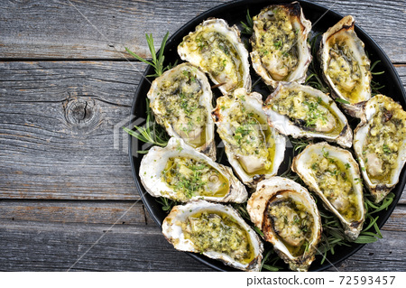 Traditional barbecue overbaked fresh opened oyster with garlic and herbs  72593457