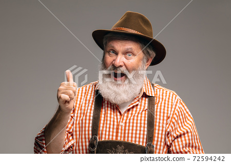 Happy senior man dressed in traditional Austrian or Bavarian costume gesturing isolated on grey studio background 72594242