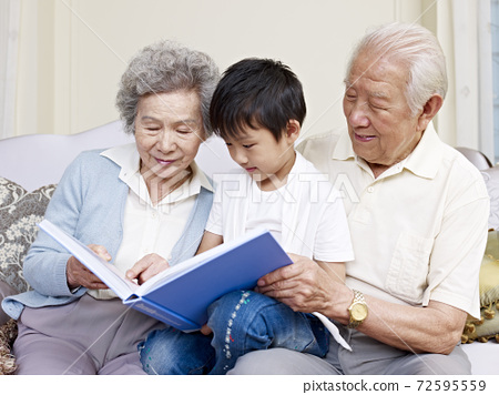 grandparents and grandson reading a book together 72595559