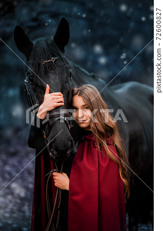 Fabulous portrait of a beautiful young lady with long brown hair, suite with red or burgundy cloak with her black horse in winter 72600827