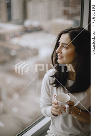 Brunette sitting on a windowsill and drinks a coffee 72601193