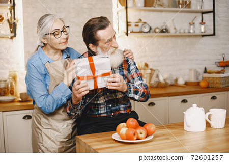 Senior couple with gifts in a kitchen 72601257