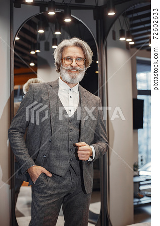 Senior man choosing a new suit in a store 72602633